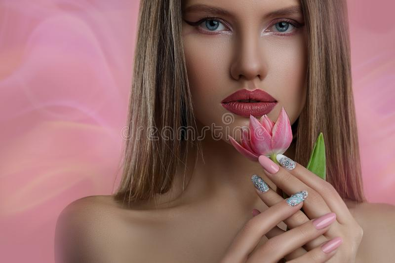 Modellera flickan med yrkesmässigt smink och spika konstmanikyr över rosa bakgrund royaltyfri fotografi