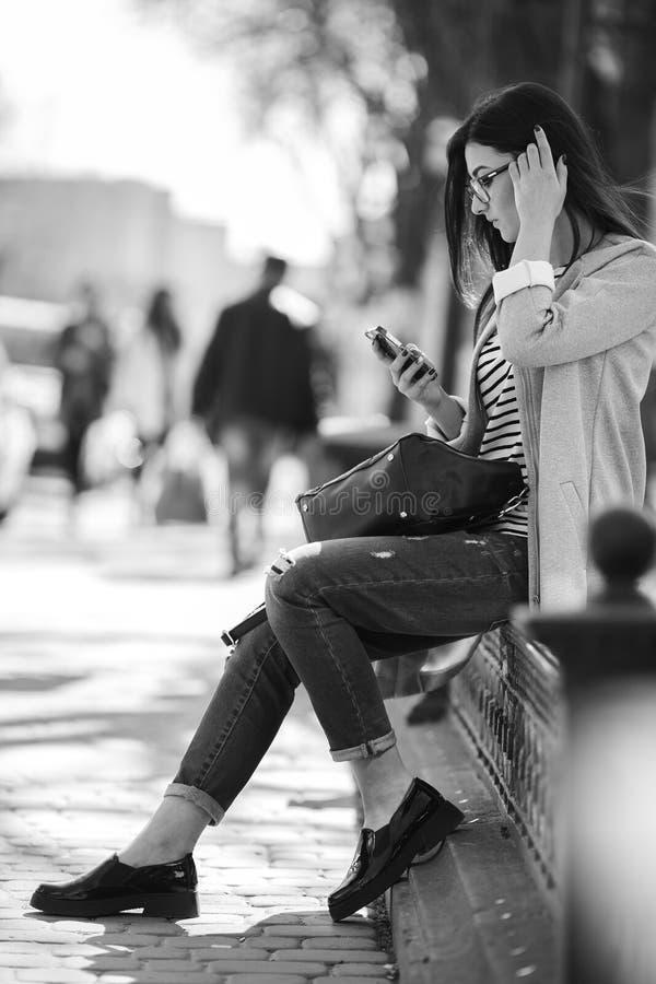 Modellera i mitt av staden med telefonen royaltyfri foto
