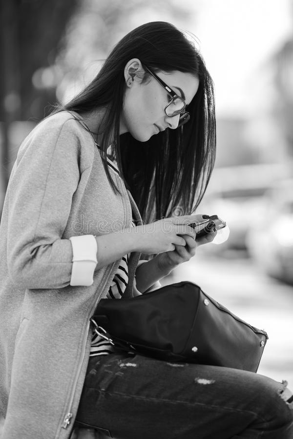 Modellera i mitt av staden med telefonen royaltyfri fotografi