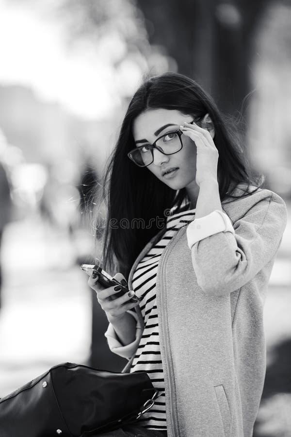 Modellera i mitt av staden med telefonen arkivbild