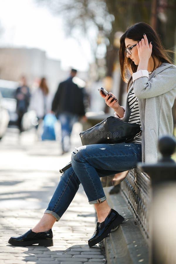 Modellera i mitt av staden med telefonen royaltyfri bild