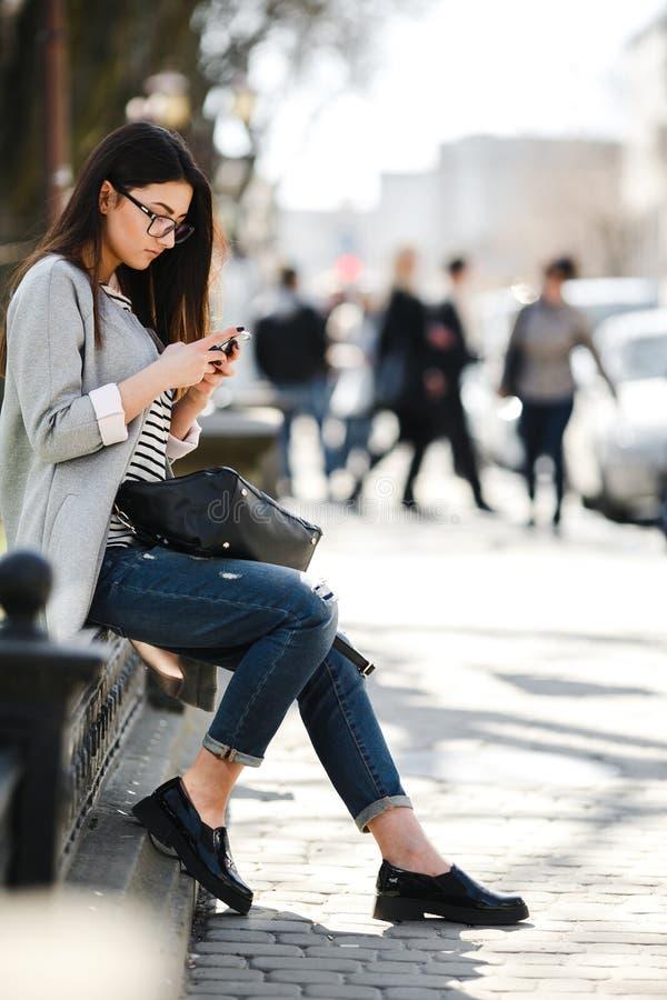 Modellera i mitt av staden med telefonen arkivfoto