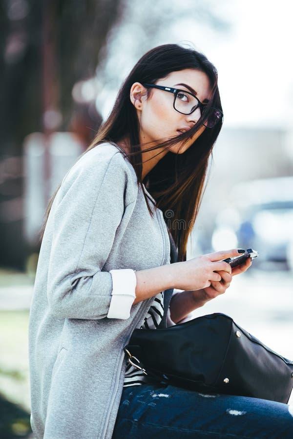Modellera i mitt av staden med telefonen royaltyfria foton