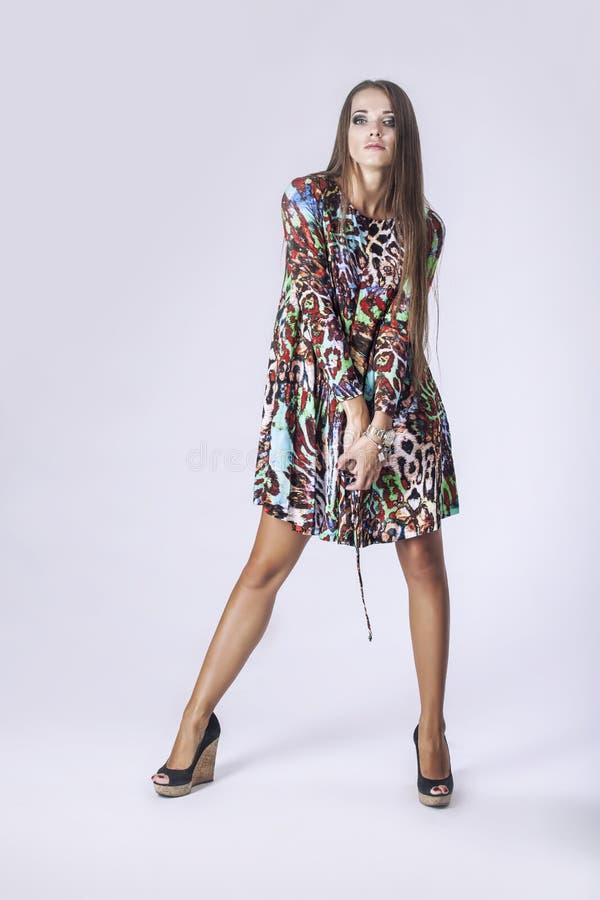 Modellera kvinnan i oavkortad längd för trendig klänning i studio på lodisar arkivfoto