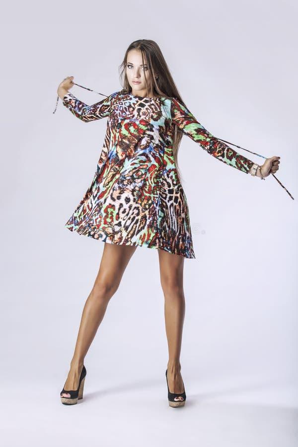 Modellera kvinnan i oavkortad längd för trendig klänning i studio på lodisar arkivbilder