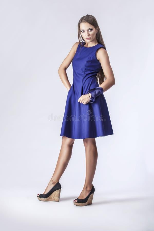 Modellera kvinnan i oavkortad längd för trendig klänning i studio på lodisar royaltyfri foto