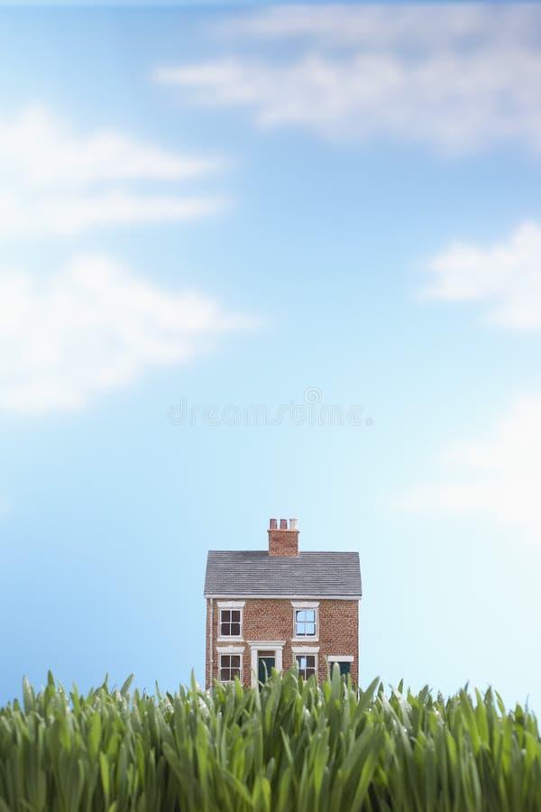 Modellhus i gräs arkivfoto