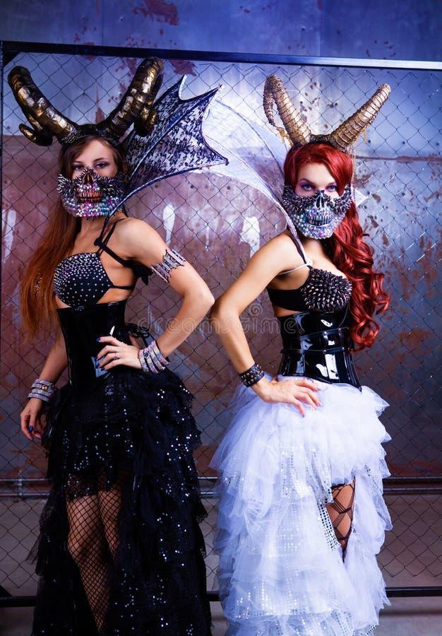 Modelli che portano il costume di Halloween di cuoio e dei corni immagini stock