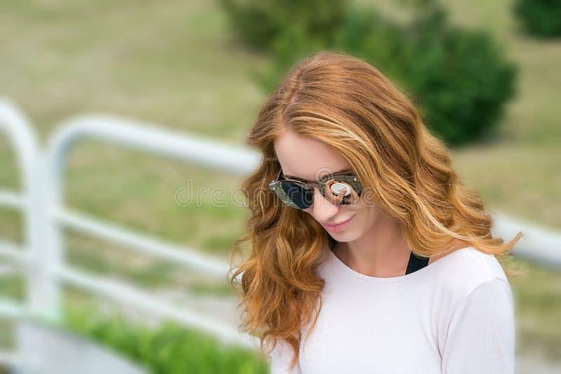 Modelli con i capelli rossi nei vetri degli occhiali da sole immagine stock