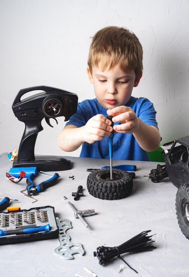 Modelli controllati radiofonici: Un ragazzino in una maglietta blu sta riparando il suo carrozzino dell'automobile di RS immagine stock libera da diritti
