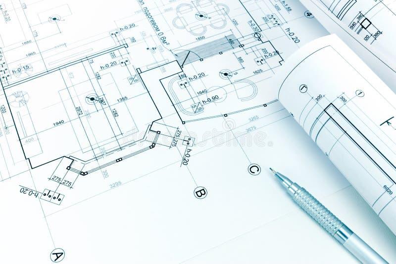 Modelli e matita architettonici rotolati sul disegno della pianta fotografia stock libera da diritti
