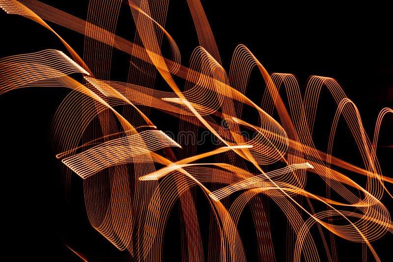 Modelli a spirale luminosi dalle strisce leggere su un fondo nero fotografia stock libera da diritti