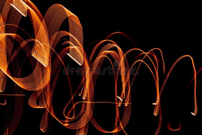 Modelli a spirale luminosi dalle strisce leggere su un fondo nero fotografie stock