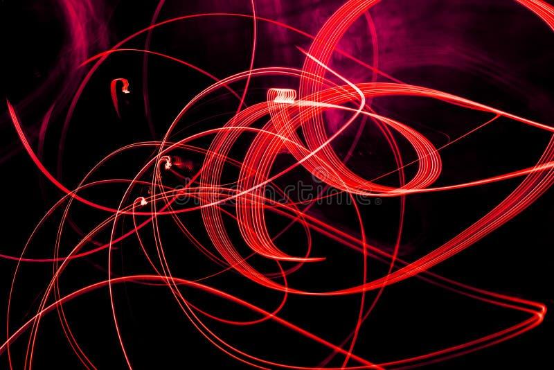Modelli a spirale luminosi dalle strisce leggere su un fondo nero fotografia stock