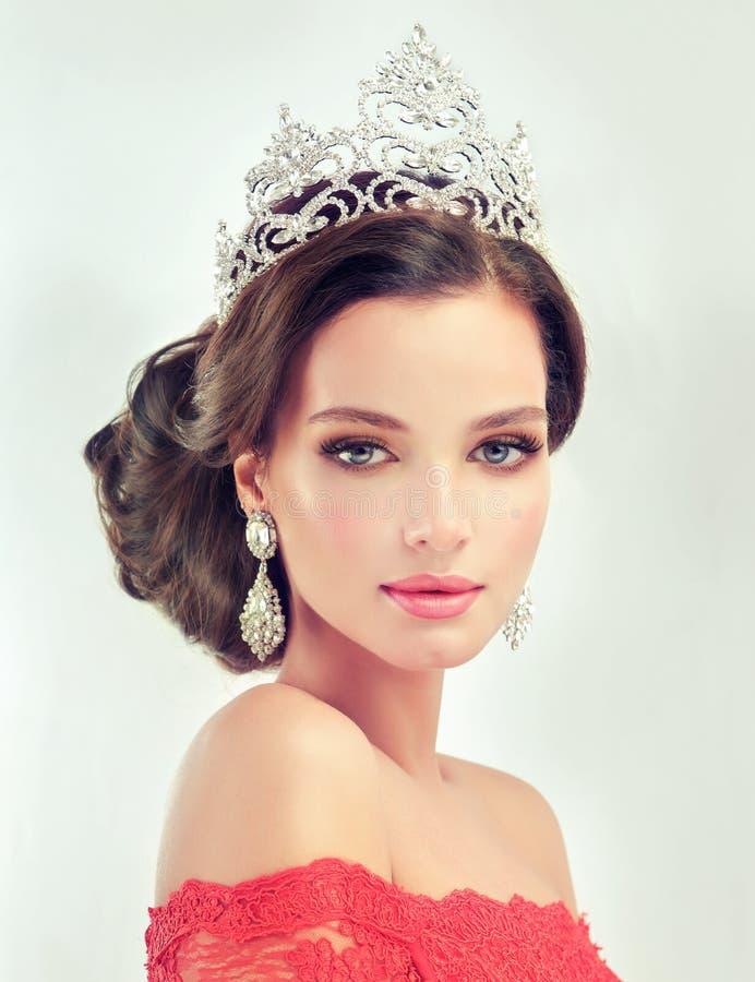 Modelli in un delicato compongono, vestito in un abito ed in una corona rossi fotografia stock