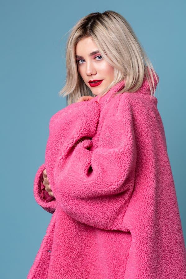 Modellieren, Mode, junge ernste Blondine des Leutekonzeptes im rosa Mantel stockbilder