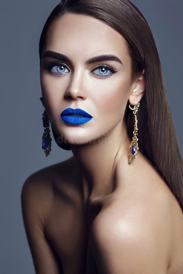 Modellieren Sie mit buntem Make-up mit den blauen Lippen und Schmuck lizenzfreies stockbild