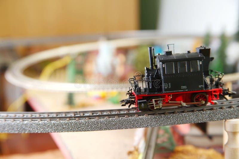 Modelljärnväg på miniatyrmodellstadplatsen arkivbild