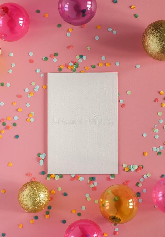 Modellkort på en rosa bakgrund med deras julpynt och konfettier Inbjudan kort, papper placera text arkivbild