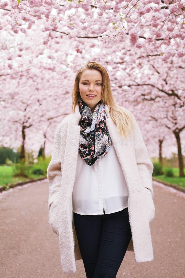 Modello abbastanza femminile che posa al giardino del fiore della molla fotografie stock