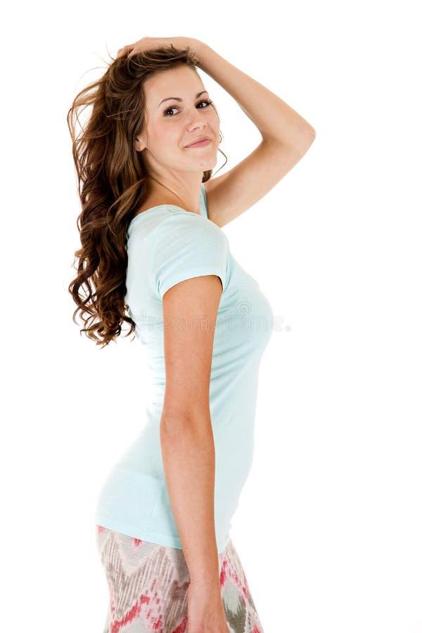Modello abbastanza femminile nella cima blu che posa lateralmente immagini stock libere da diritti