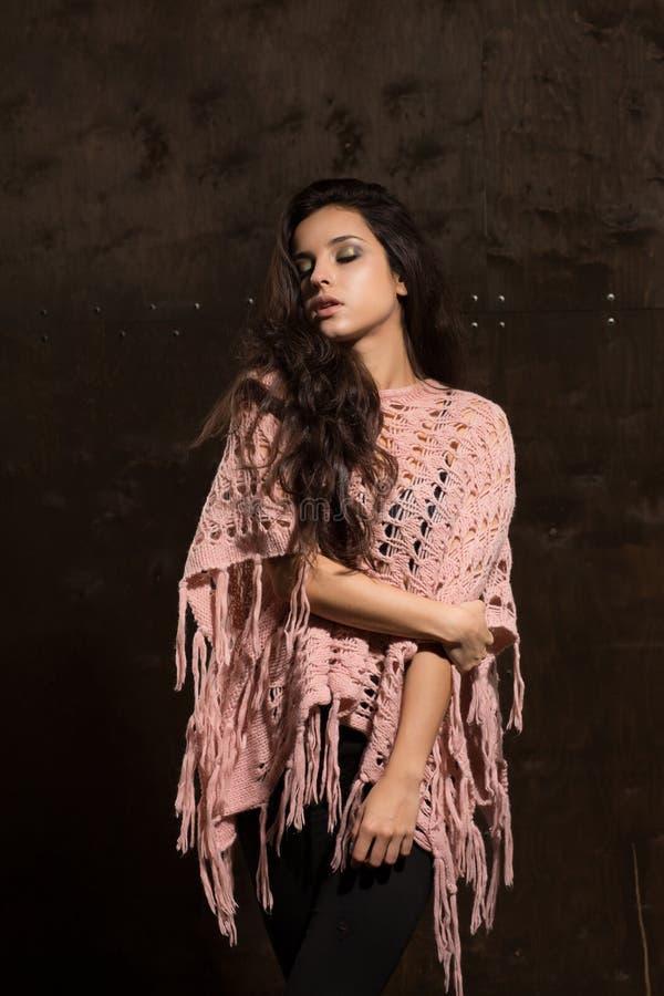 Modello abbronzato affascinante con capelli fertili lunghi che posano in maglione sopra immagini stock libere da diritti