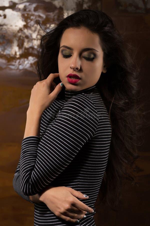 Modello abbronzato attraente con trucco professionale che posa allo studi fotografia stock libera da diritti