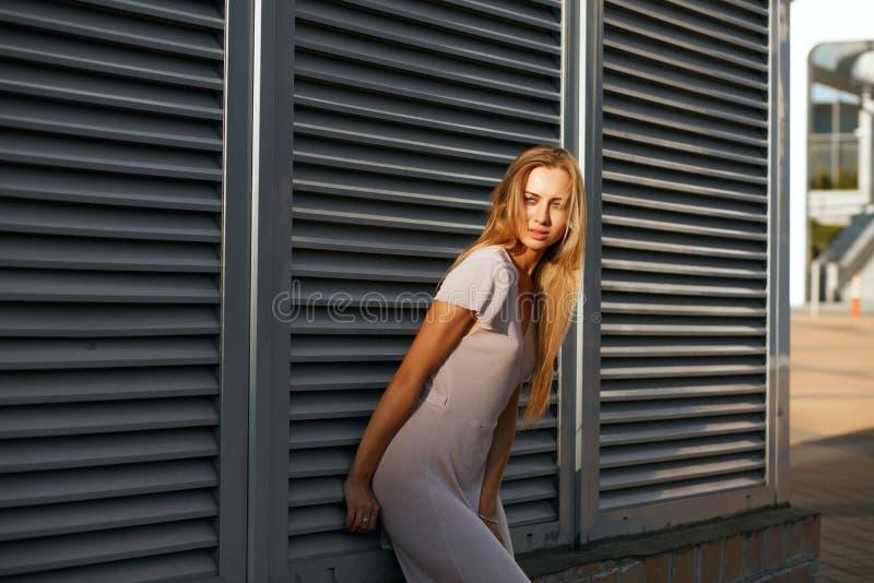 Modello abbronzato di stupore in attrezzatura alla moda che posa al backgro immagini stock