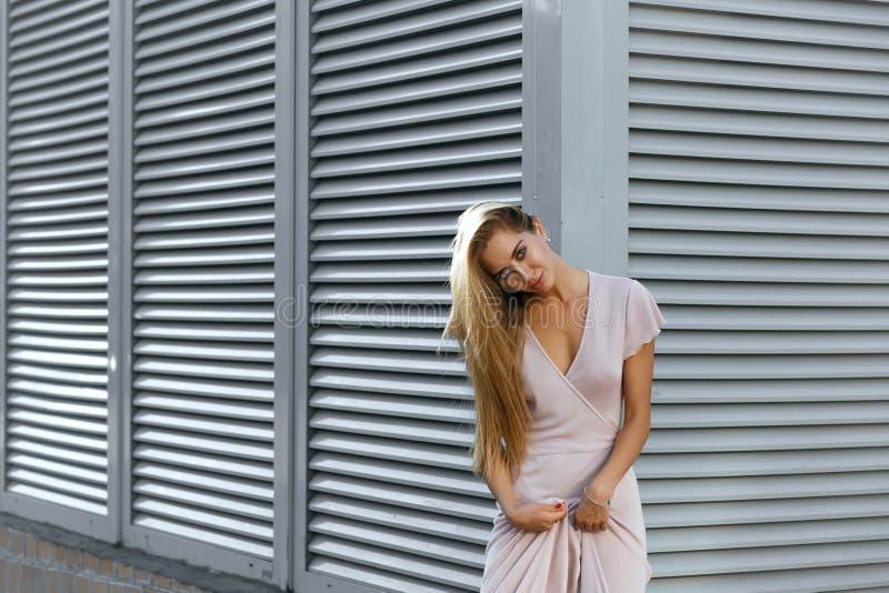 Modello abbronzato sexy in attrezzatura alla moda che posa ai precedenti immagine stock