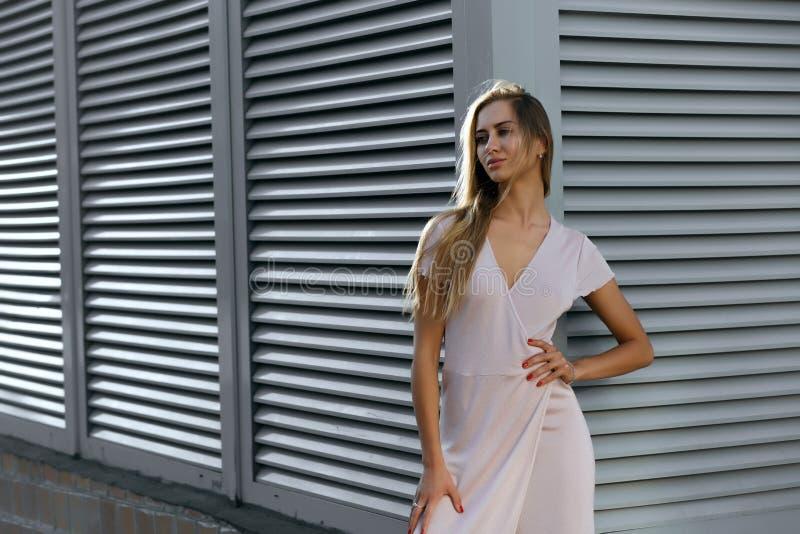 Modello abbronzato splendido in attrezzatura alla moda che posa al backgr fotografia stock libera da diritti