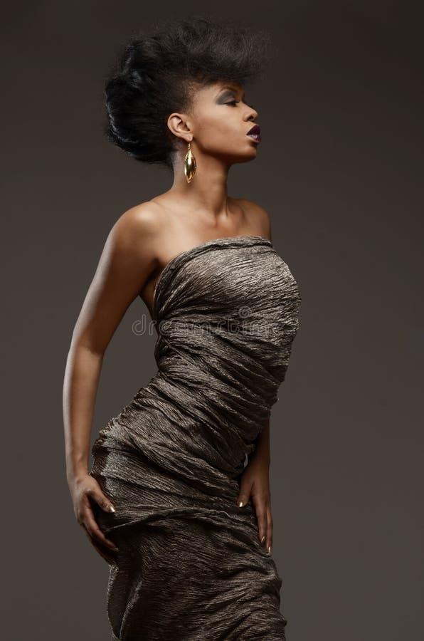 Modello afroamericano di alta moda eccellente che posa in un vestito dal metallo fotografia stock libera da diritti