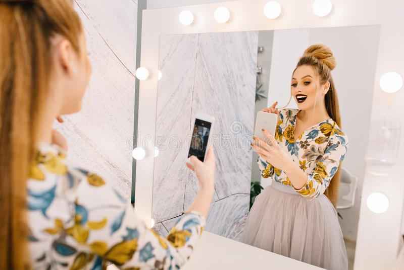 Modello alla moda con pettinatura alla moda, trucco professionale che fa selfie in specchio nel salone del parrucchiere esprimere immagini stock