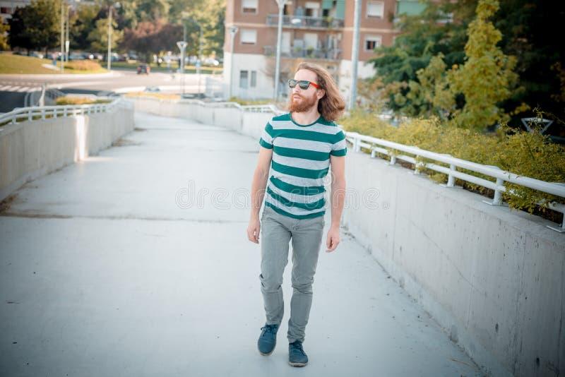 Modello alla moda dei pantaloni a vita bassa con lo stile di vita rosso lungo della barba e dei capelli fotografia stock libera da diritti