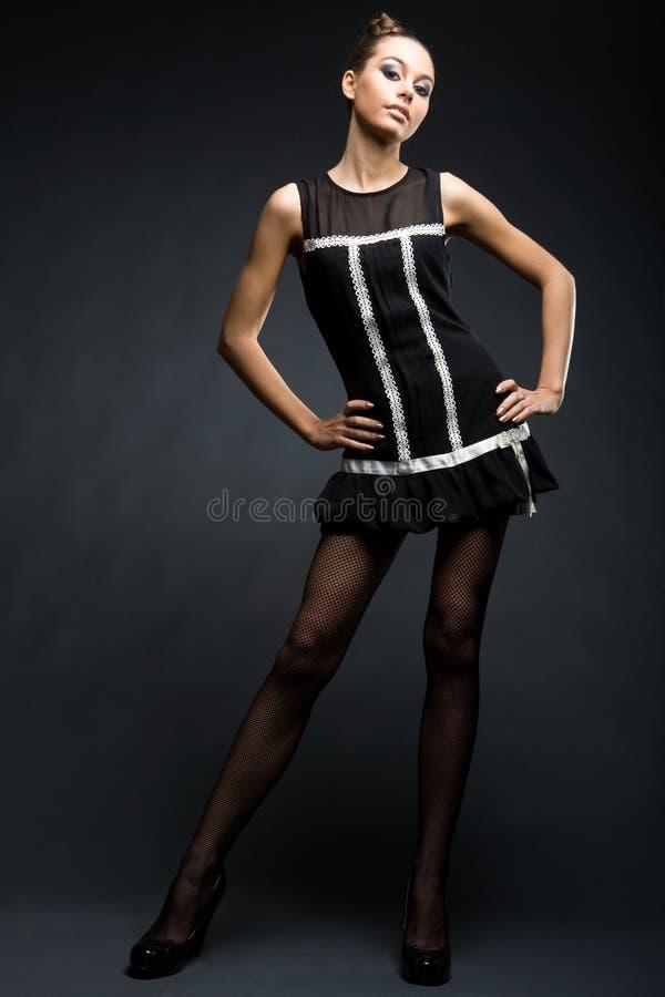 Modello alla moda della ragazza in vestito nero immagine stock