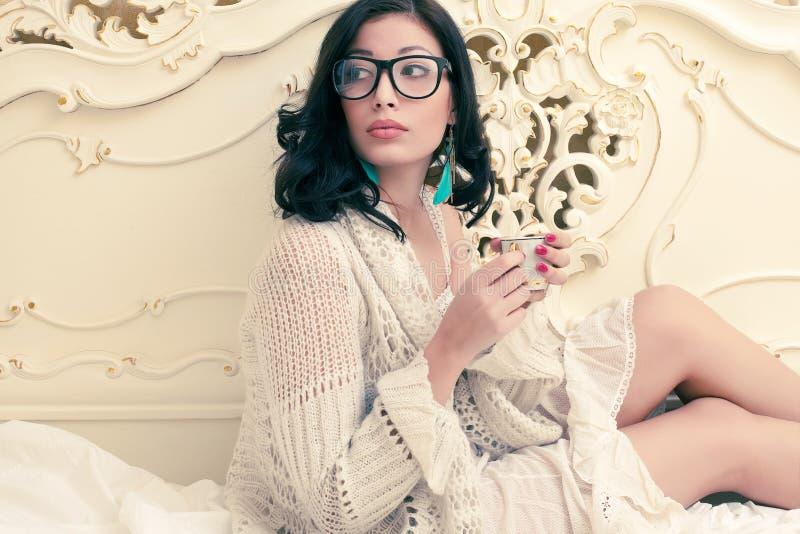 Modello alla moda in vetri d'avanguardia che bevono tè fotografia stock libera da diritti