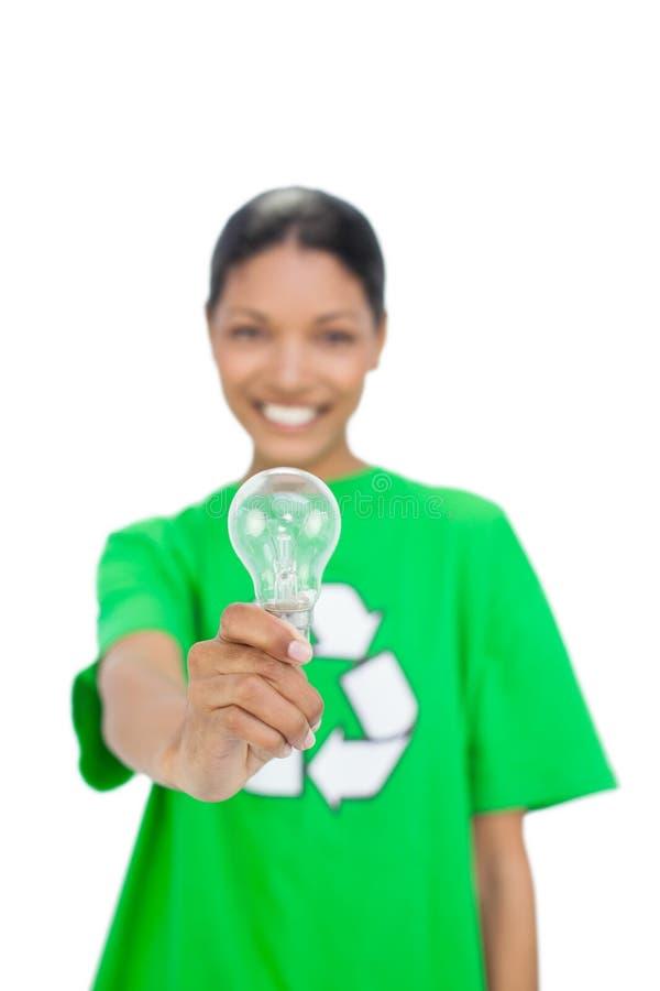 Modello allegro che dura riciclando maglietta che tiene lampadina immagine stock libera da diritti