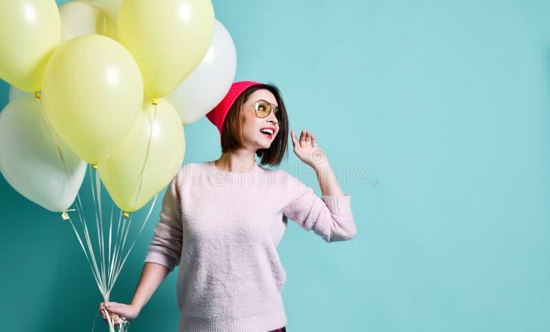 Modello allegro divertendosi e celebrando con il pallone di colore pastello immagini stock libere da diritti