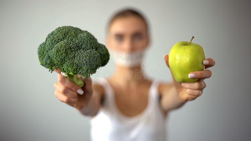 Modello anoressico con la bocca legata che tiene le verdure, concetto di eccessivo digiuno immagine stock