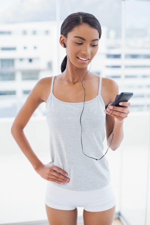 Modello attraente felice in abiti sportivi che ascoltano la musica fotografie stock libere da diritti