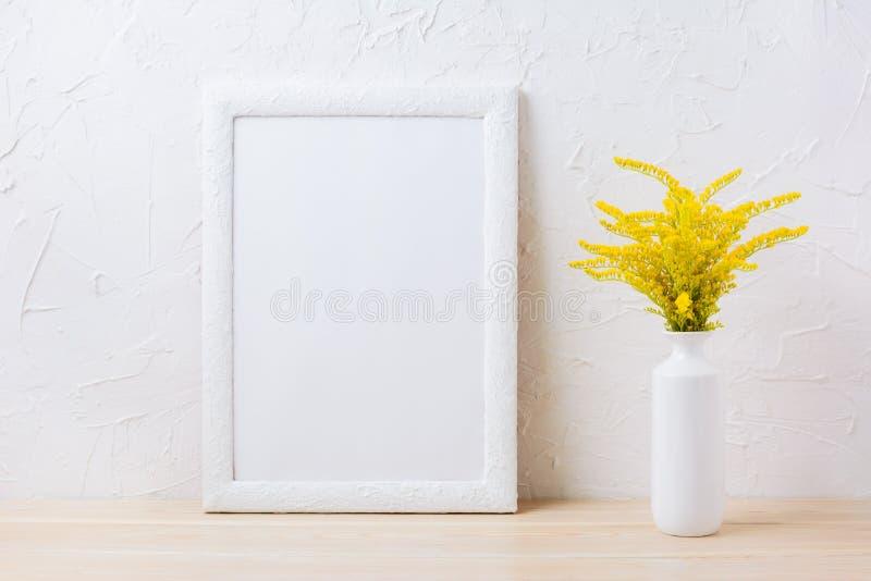 Modello bianco della struttura con erba di fioritura gialla ornamentale in vaso fotografia stock libera da diritti