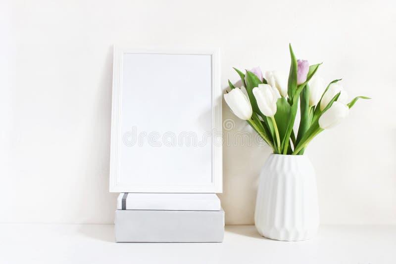Modello in bianco bianco della struttura di legno con il mazzo della molla dei tulipani in vaso della porcellana ed il mucchio de immagini stock