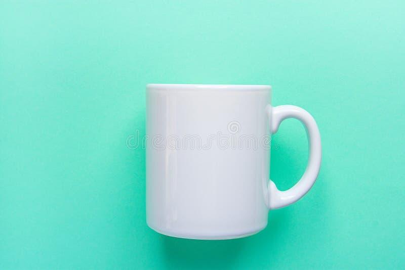 Modello bianco in bianco della tazza sul fondo leggero del turchese Spazio del modello per l'iscrizione creativa del materiale il immagini stock
