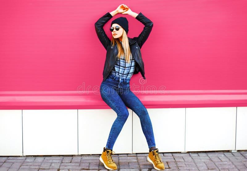 Modello biondo alla moda della ragazza in rivestimento nero d'uso di posa integrale di stile della roccia, cappello sulla via del fotografia stock libera da diritti