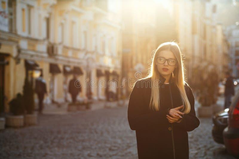 Modello biondo di fascino con il cappotto d'uso dei capelli lunghi, posante nell'abbagliamento del sole Spazio vuoto fotografia stock