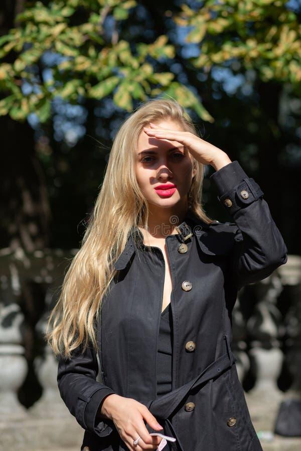 Modello biondo grazioso con trucco luminoso che indossa cappotto nero ed il co fotografie stock