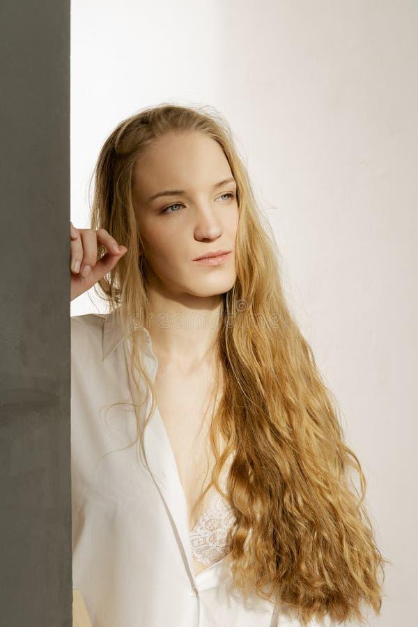Modello biondo incantante con capelli lunghi in camicia bianca su fondo bianco immagini stock