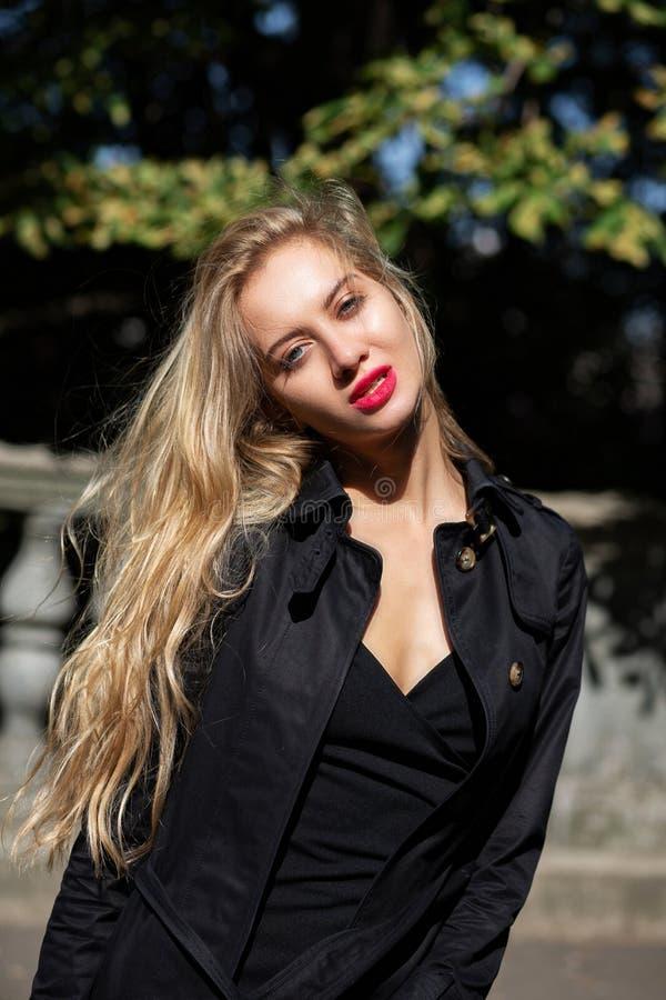 Modello biondo magnifico con trucco luminoso che porta cappotto nero a immagini stock