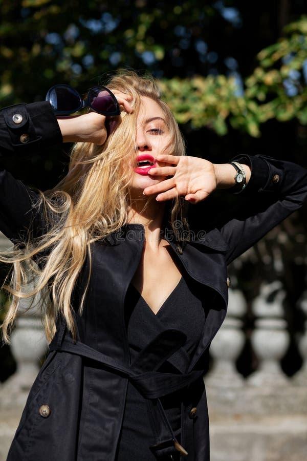 Modello biondo sensuale che porta cappotto nero e vestito che posano nei raggi immagine stock