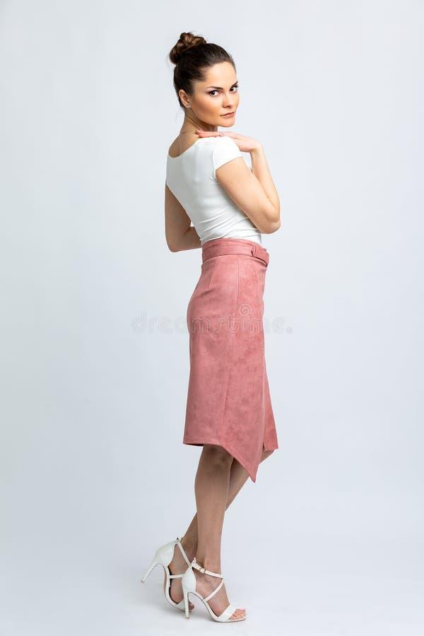 Modello in blusa bianca, gonna rosa della pelle scamosciata con la cinghia, sandali bianchi, con la catena d'argento intorno al c immagine stock libera da diritti