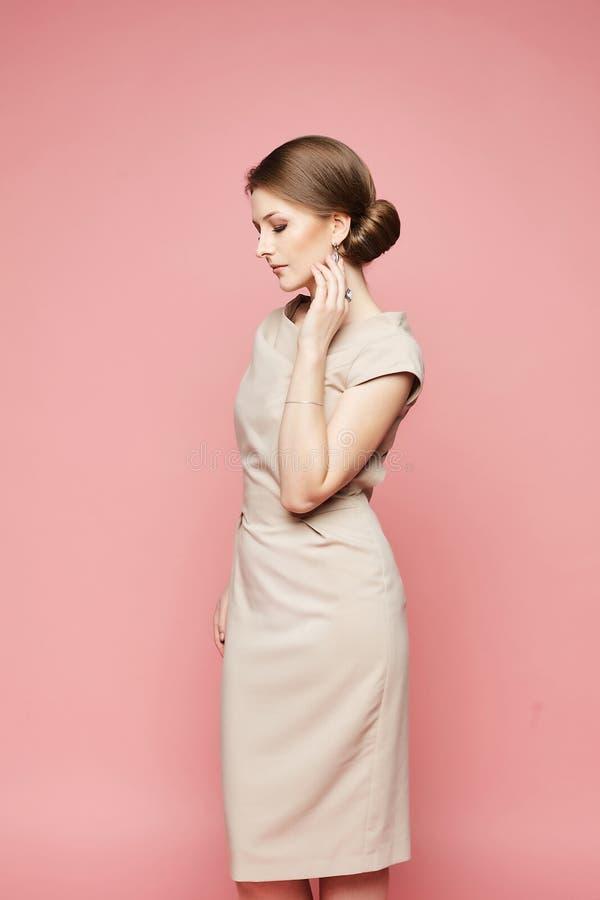 Modello castana alla moda, bella donna con l'acconciatura alla moda in vestito d'avanguardia beige che posa con gli occhi chiusi  immagini stock